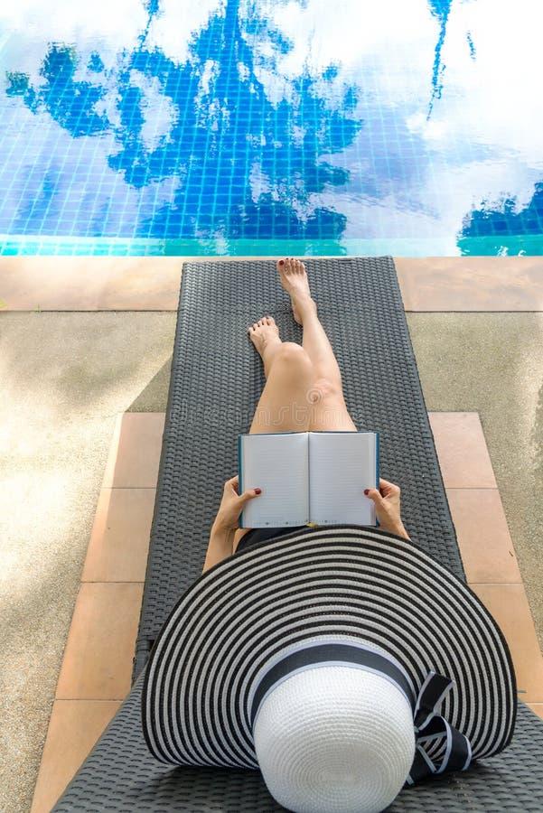 Sommartid och semestrar Kvinnalivsstilkoppla av och läsebok i lyxig simbassängsunbath, sommardag på strandresoen royaltyfri bild