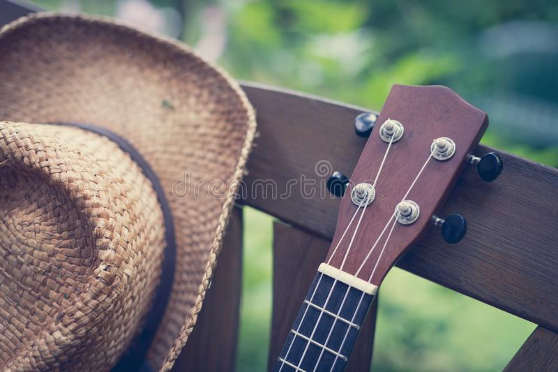 Sommartid: Ukulelet med gul solglasögon på ett trä parkerar bänken royaltyfri fotografi