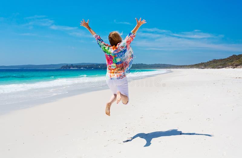 Sommartidkvinnan hoppar för glädjestrand royaltyfria bilder