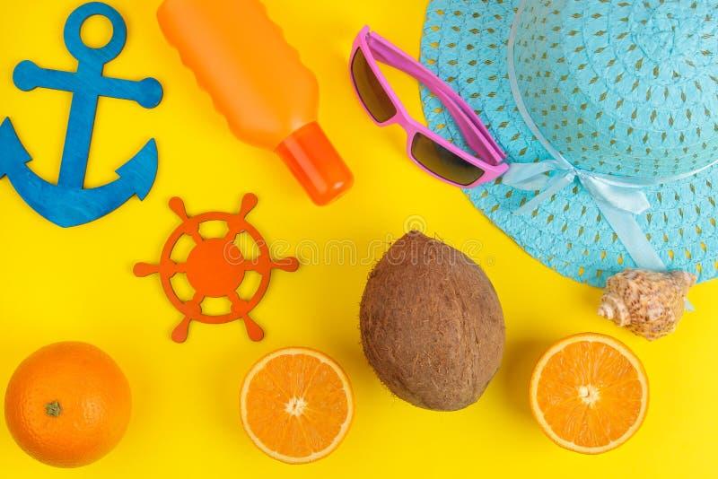 Sommartillbehör Begrepp av sommarsemestrar sunscreen, hatt, kokosnöt, apelsin och exponeringsglas på en ljus gul bakgrund Top bes fotografering för bildbyråer