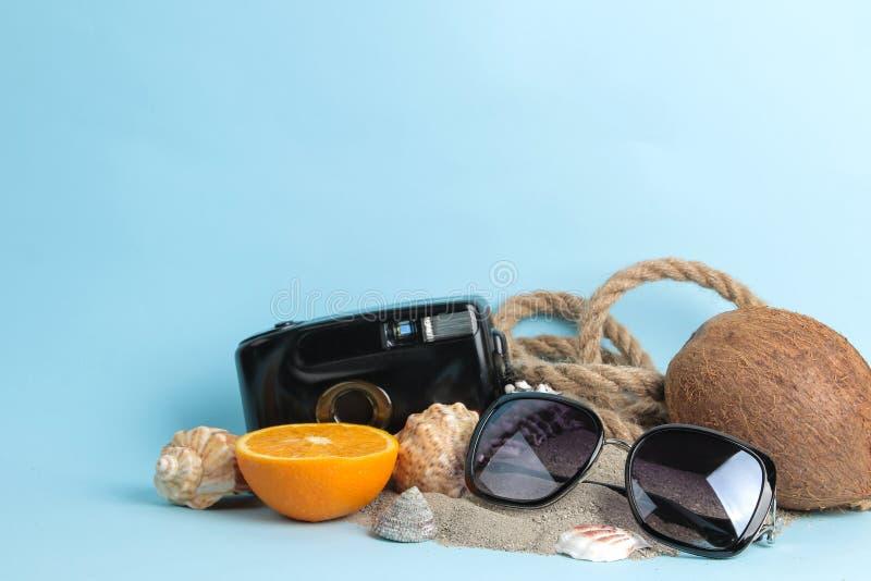 sommartillbehör med kokosnöten, apelsinen och skal, fotokamera på en ljus blå bakgrund fritt avstånd royaltyfri bild