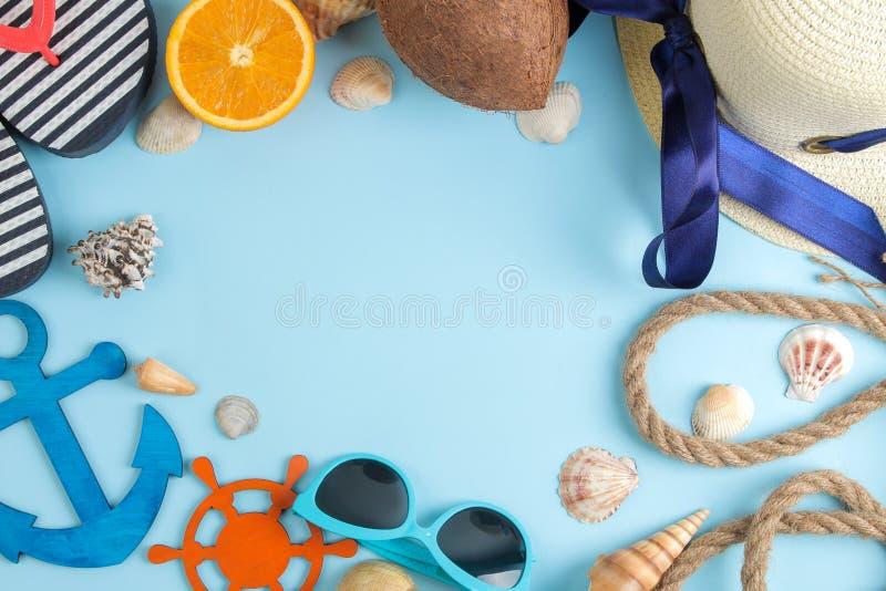 Sommartillbehör med kokosnöten, apelsinen, solexponeringsglas och skal, på en ljus blå bakgrund fritt avstånd Top beskådar Ram royaltyfri bild
