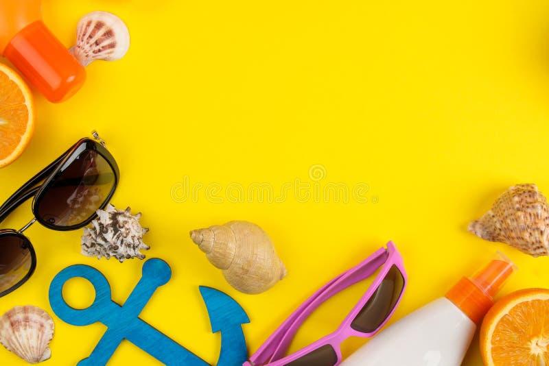 Sommartillbehör med skal, solexponeringsglas, apelsinen och kokosnöten på en ljus gul bakgrund Top beskådar Utrymme för text royaltyfria bilder