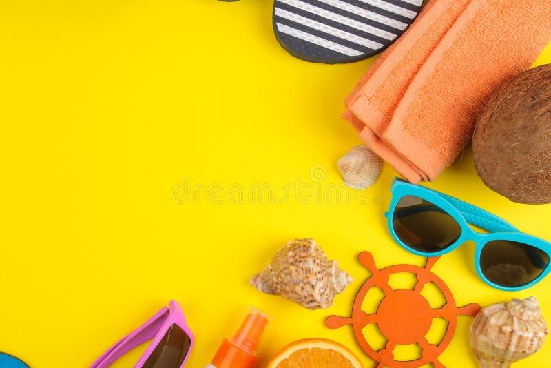 Sommartillbehör med skal, solexponeringsglas, apelsinen och kokosnöten på en ljus gul bakgrund Top beskådar Utrymme för text fotografering för bildbyråer