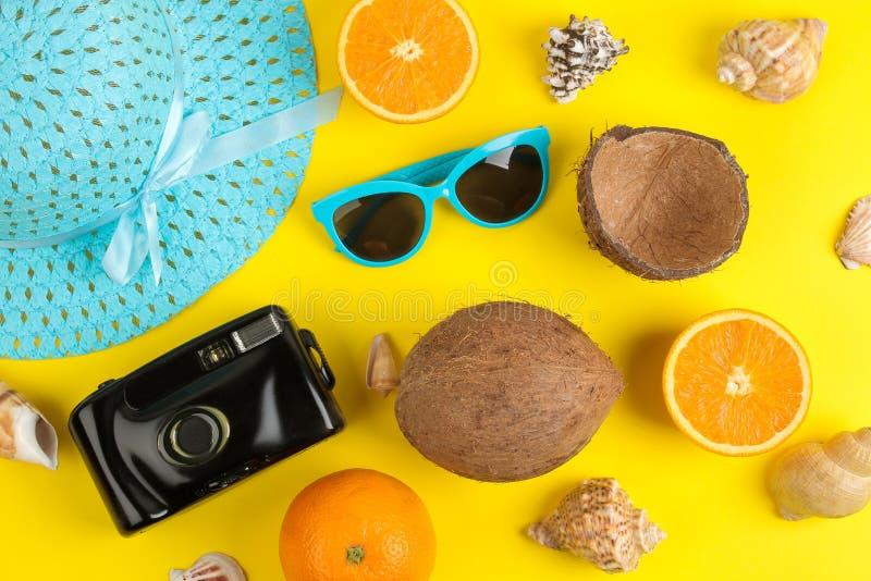 sommartillbehör med solexponeringsglas, hatten, skal, kameran och kokosnöten på en ljus gul bakgrund Top beskådar royaltyfria bilder