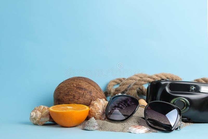 sommartillbeh?r med kokosn?ten, apelsinen och skal, fotokamera p? en ljus bl? bakgrund fritt avst?nd fotografering för bildbyråer
