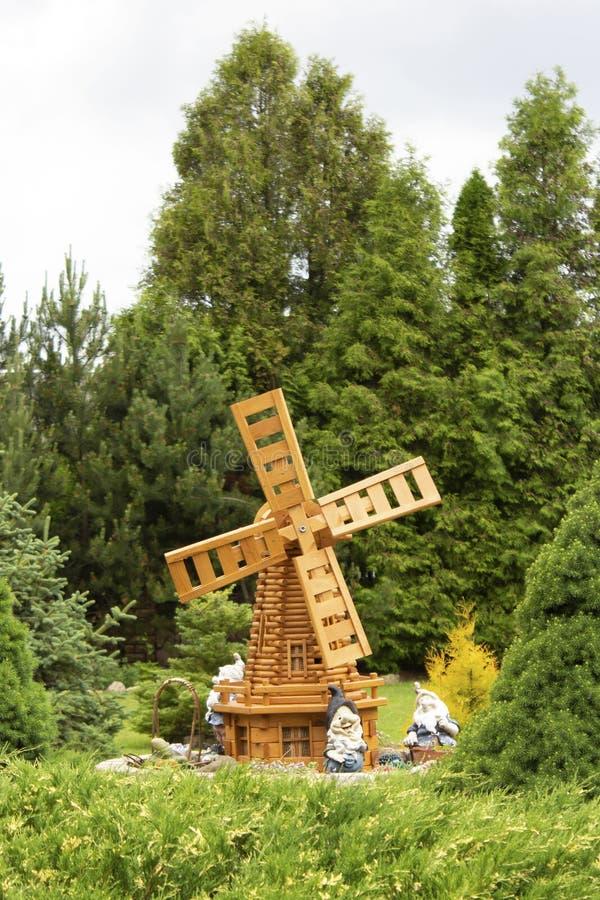 Sommarträdgård med en dekorativ väderkvarn och gnomer royaltyfri foto