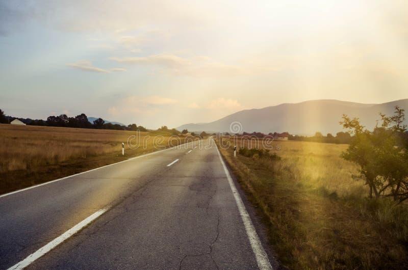 Sommarväg med solstrålarna bakgrundsfokusberg skidar arkivfoto