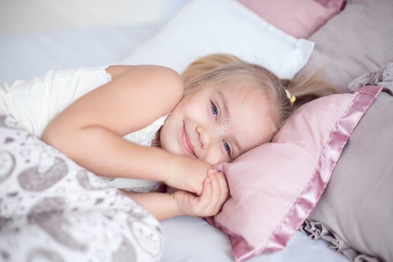 Sommeil adorable en gros plan de petite fille dans le lit avec les yeux ouverts photo stock