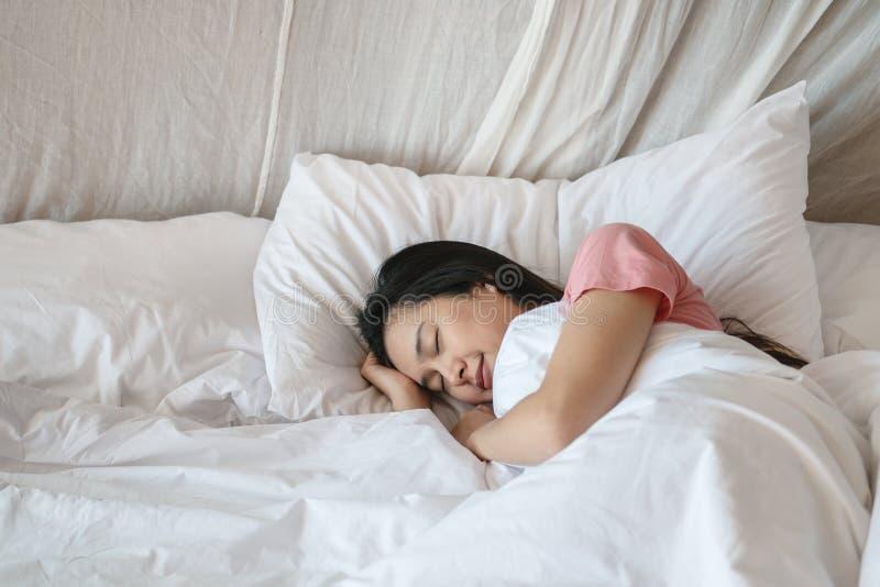 Sommeil asiatique de femme de plan rapproch? sur le lit sous la couverture ? l'arri?re-plan de chambre ? coucher pendant le matin photo stock