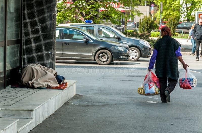 Sommeil aux pieds nus de femme de sans-abri sur la rue urbaine dans la ville sur le trottoir près du bâtiment tandis que les gens images libres de droits