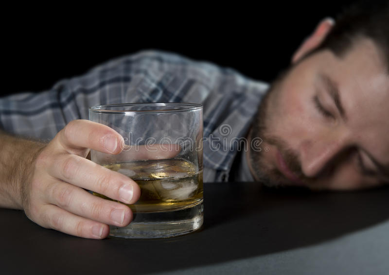 Sommeil bu par homme alcoolique d'intoxiqué jugeant le whiskey en verre dans le concept d'alcoolisme image stock