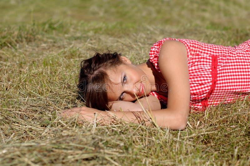 Sommeil de femme sur l'herbe verte photo stock