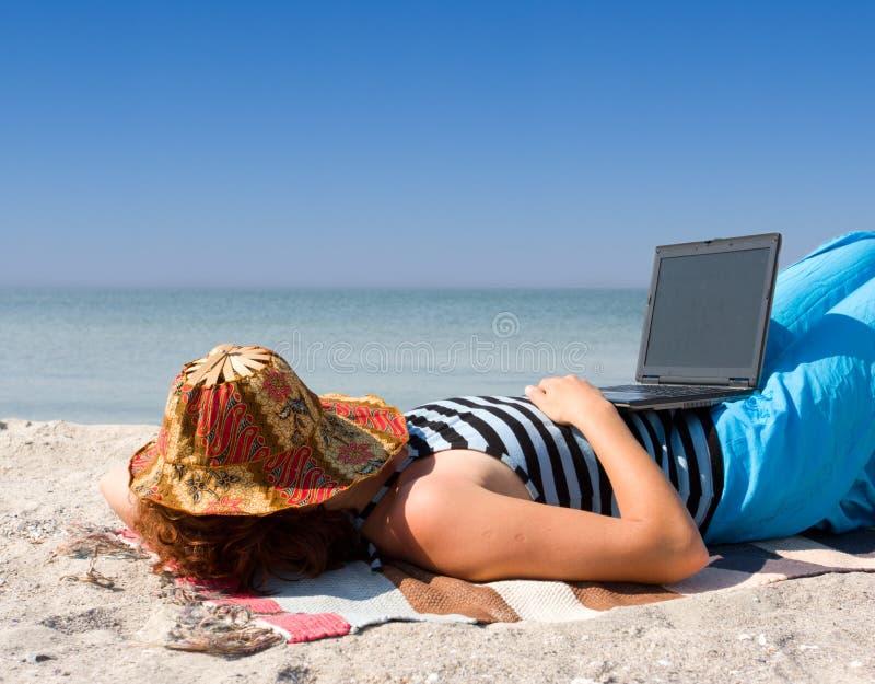Sommeil de fille avec l'ordinateur portable à la plage de mer photos stock