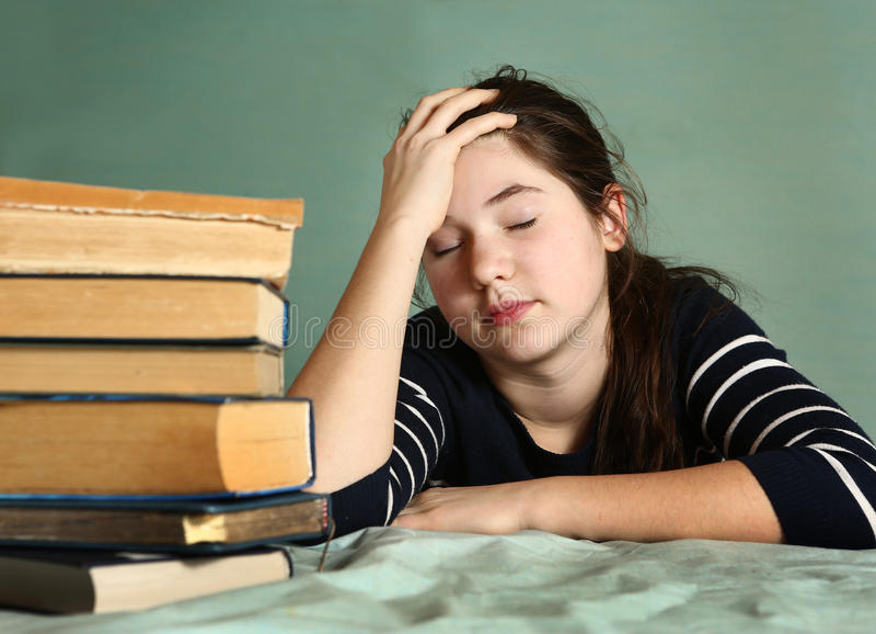 Sommeil fatigué d'adolescente parmi des livres photos stock