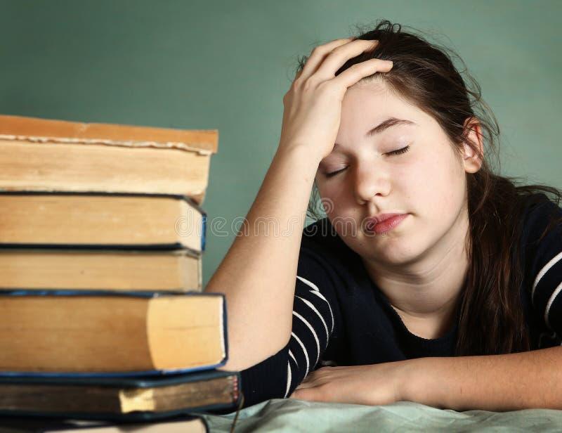 Sommeil fatigué d'adolescente parmi des livres photo stock