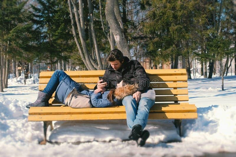 Sommeils de femme, regard d'homme au téléphone Équipez et un repos de femme ensemble sur un banc en parc de ville d'hiver Jour d' photo stock