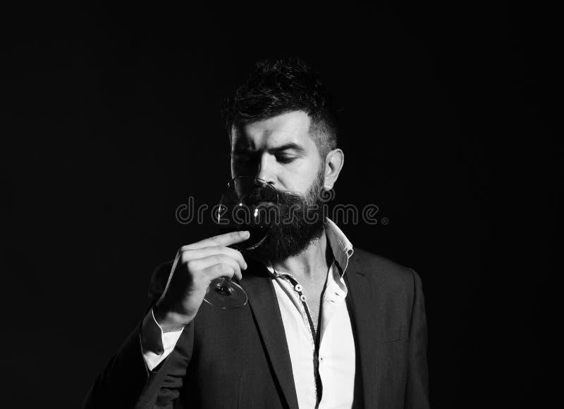 Sommelier avec la barbe sur le fond vert Connaisseur avec le visage sérieux goûtant le vin cher de cabernet photo libre de droits