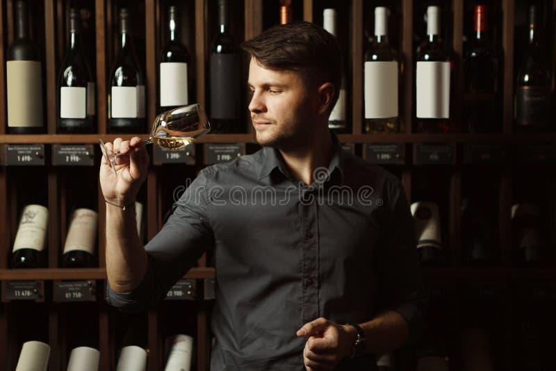 Sommelier bekijkt witte wijn in glas in kelder stock afbeelding