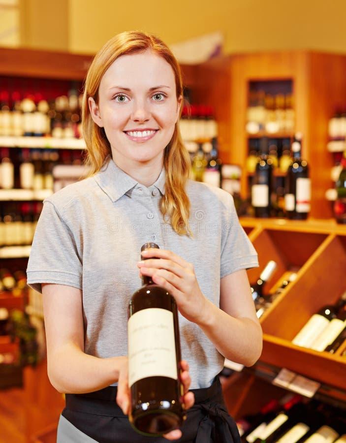 Sommelier in bottiglia di raccomandazione del negozio di vino di vino fotografie stock libere da diritti