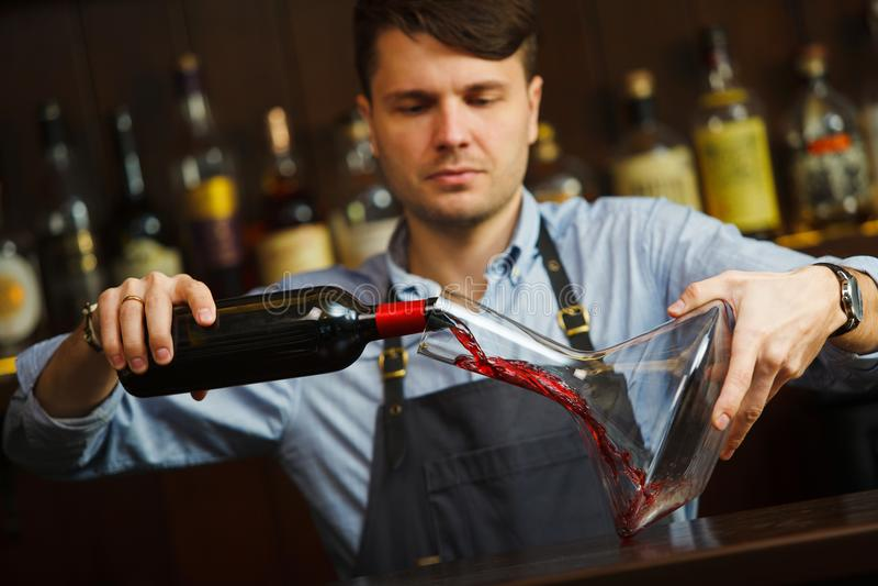 Sommelier dolewania wino w szkło od dekantatoru męski kelner fotografia stock