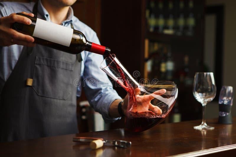 Sommelier dolewania wino w szkło od dekantatoru męski kelner obrazy stock
