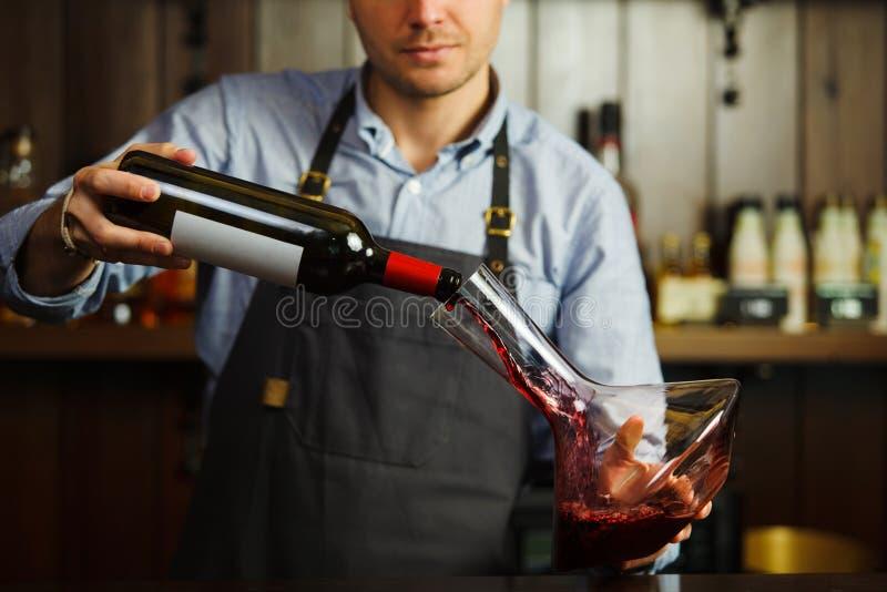 Sommelier dolewania wino w szkło od dekantatoru męski kelner zdjęcia stock
