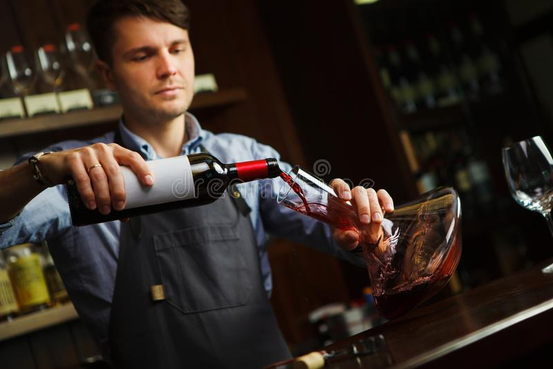 Sommelier dolewania wino w szkło od dekantatoru męski kelner fotografia royalty free