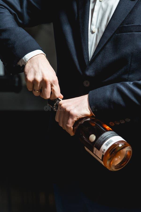 Sommelier em uma obscuridade - o casaco azul abre uma garrafa do vinho cor-de-rosa foto de stock royalty free