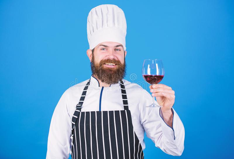 Sommelier examining wine. This wine is just perfect. Professional chef in cook uniform. Confident male sommelier royalty free stock image