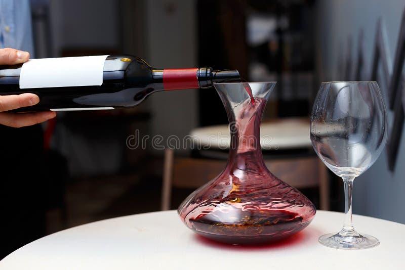 Sommelier giet wijn in een karaf royalty-vrije stock foto's