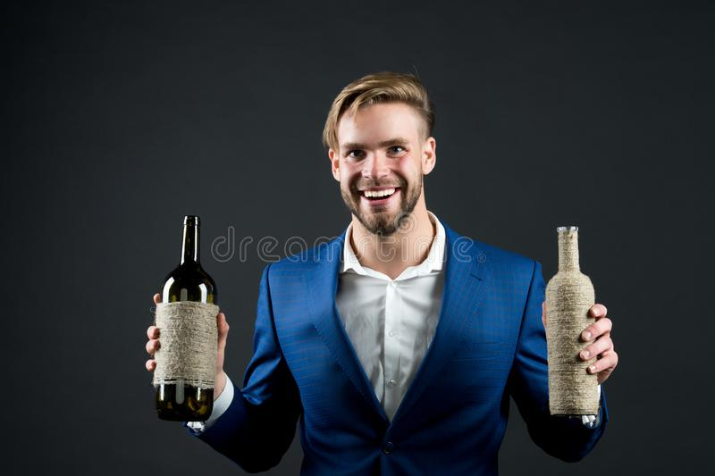 Sommelier hold two bottles of wine. Professional wine degustation concept. Man formal suit with wine bottles in hands. Sommelier handsome cheerful guy on dark royalty free stock photo