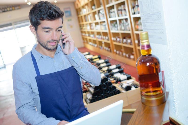 Sommelier im vorderen Laptop am Weinkeller stockfoto