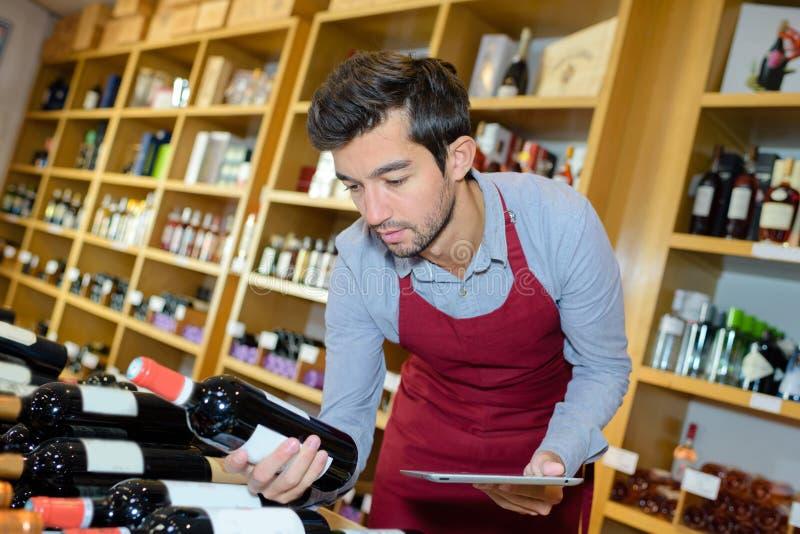 Sommelier joven que sostiene el vino de la botella imagenes de archivo