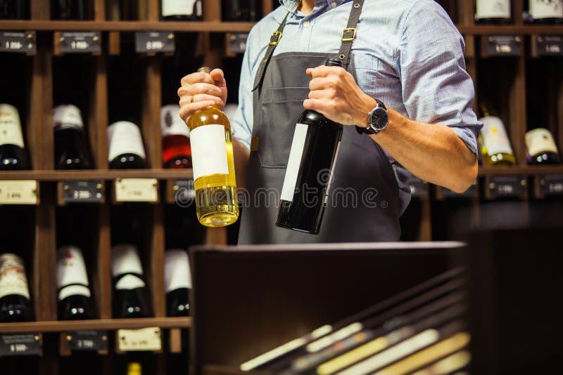Sommelier joven que sostiene la botella de vino rojo en sótano fotos de archivo