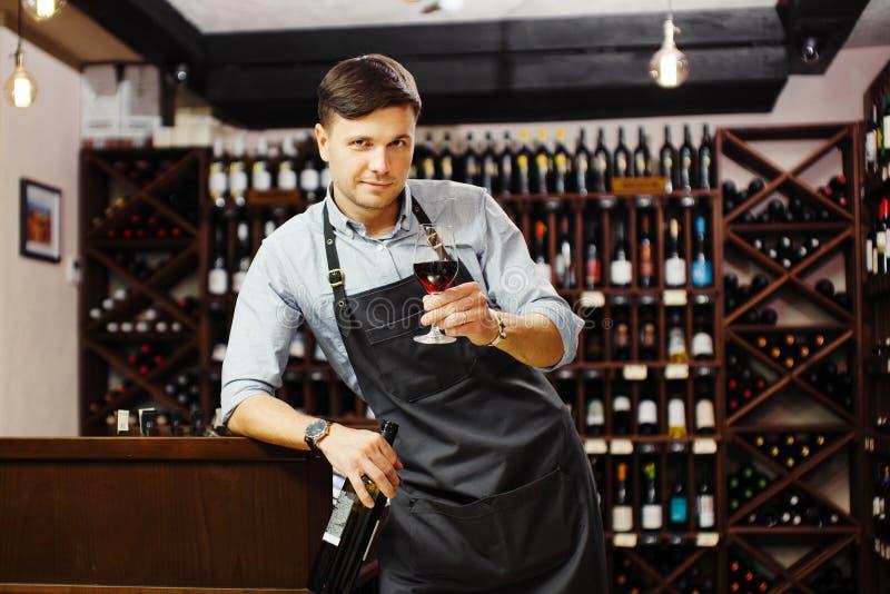 Sommelier masculin goûtant le vin rouge dans la cave Expert en matière professionnel de degustation photographie stock