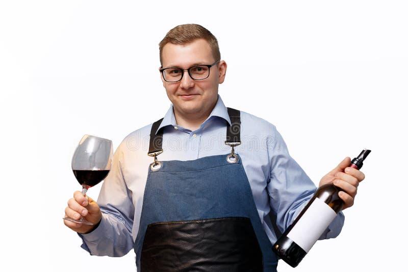 Sommelier masculino con una botella de vino tinto y de un vidrio imagenes de archivo