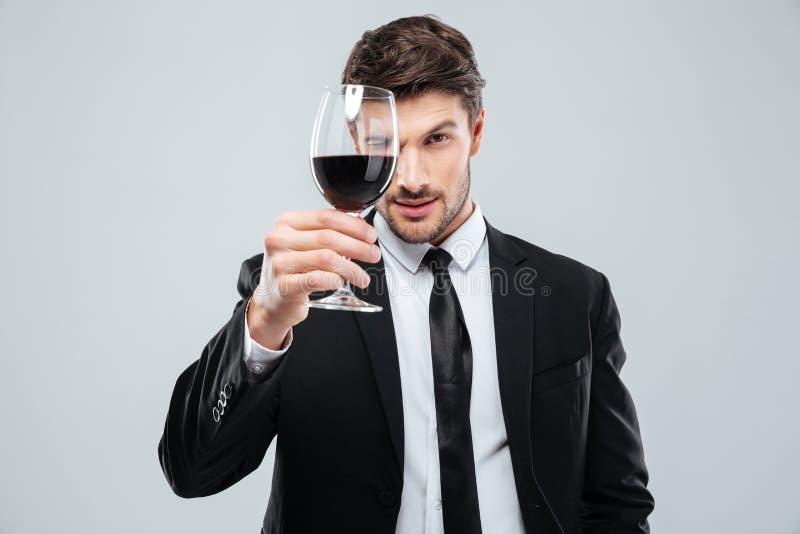 Sommelier masculino joven enfocado que mira el vino rojo en vidrio fotografía de archivo libre de regalías