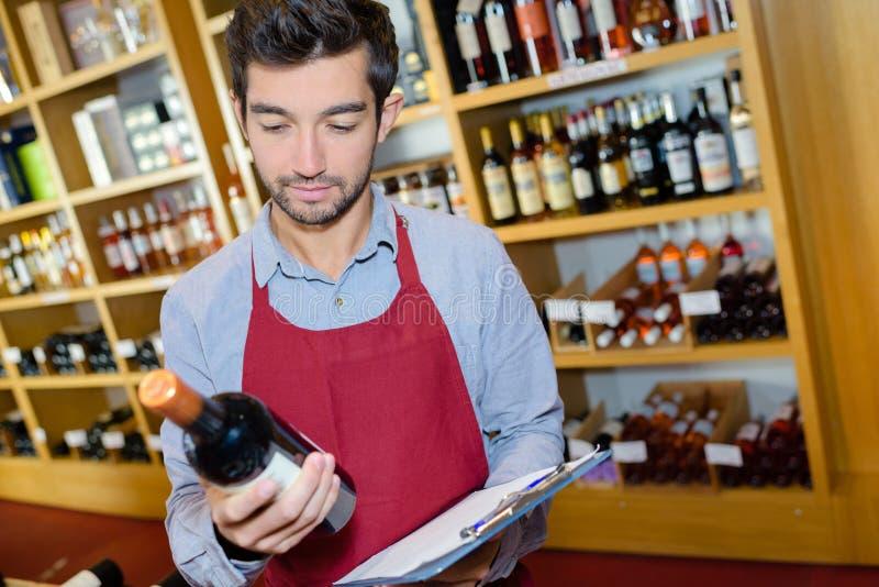 Sommelier mit dem Flaschenwein, der nahe gut gefüllt Regalen steht lizenzfreie stockbilder