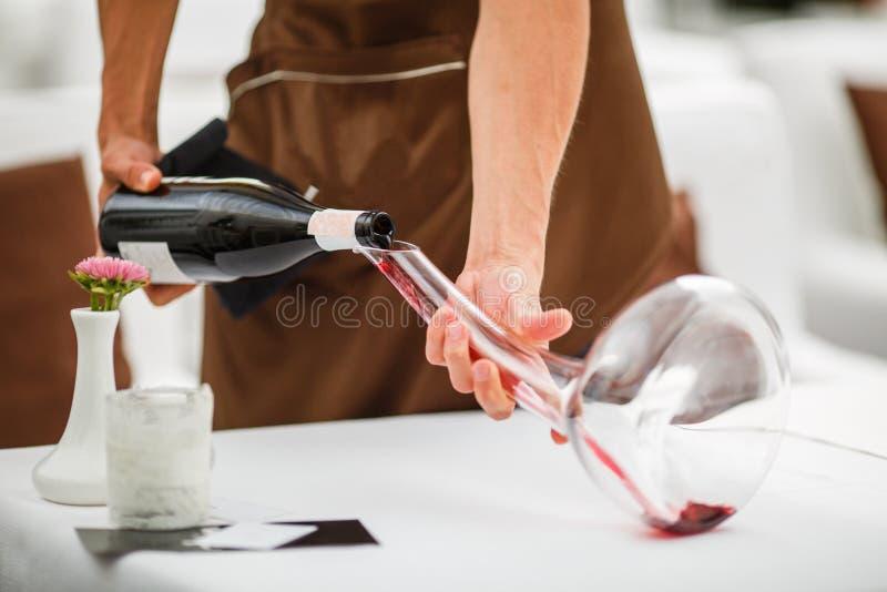 Sommelier nalewa czerwone wino w szklanego dekantator obrazy stock