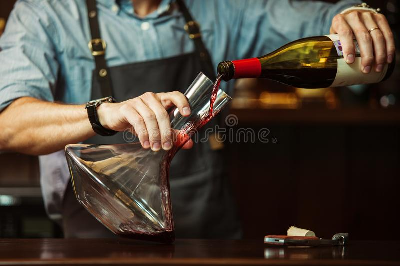 Sommelier pouring red wine into carafe to make perfect color. Sommelier pouring out red wine into glass carafe to make perfect color of red wine. Male waiter stock photo