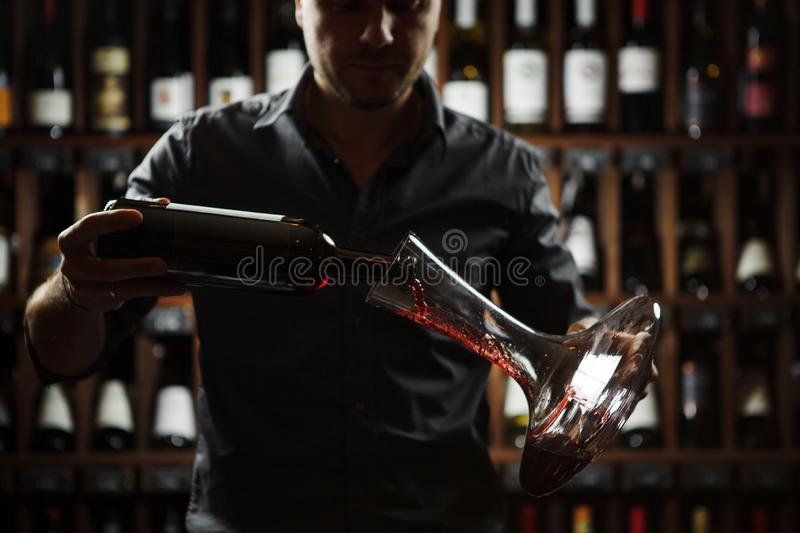 Sommelier pouring red wine in decanter, backlight shot stock images