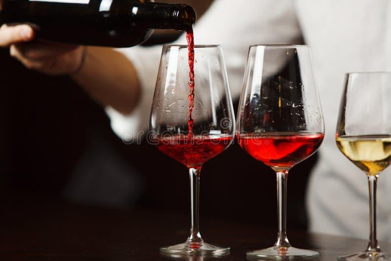 Sommelier que derrama tipos diferentes de vinho fino imagens de stock