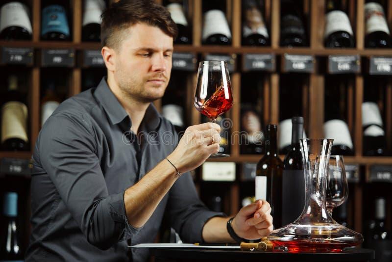 Sommelier que mira la copa de vino roja con la bebida fotografía de archivo