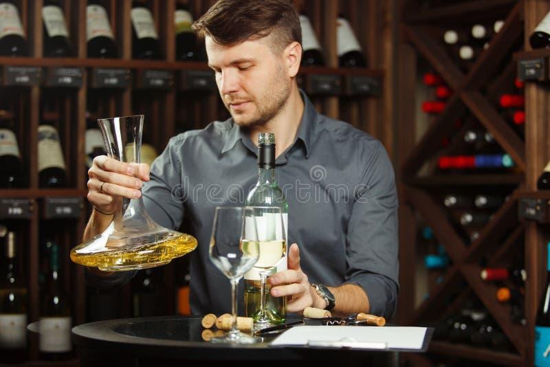 Sommelier que sostiene la jarra en manos llena de vino foto de archivo