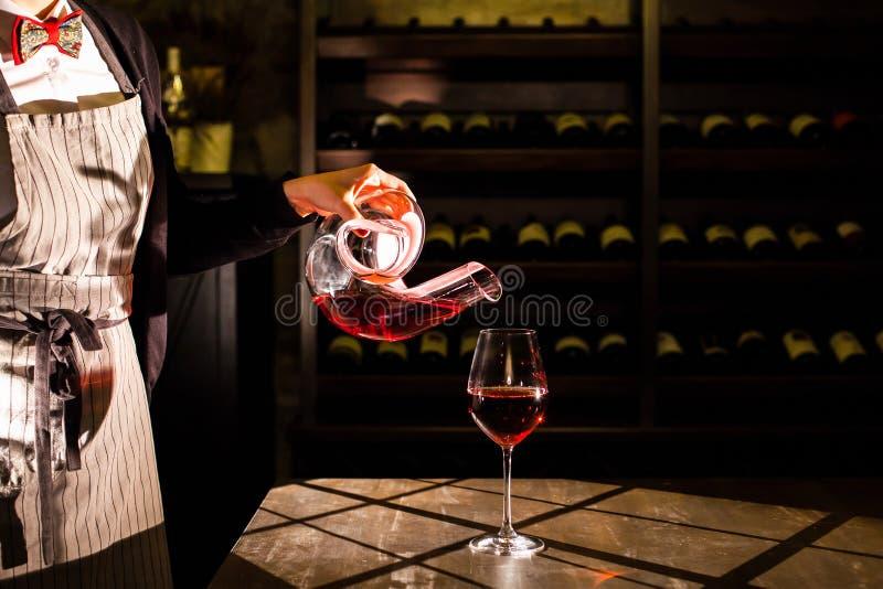 Sommelier que sostiene una garrafa con el vino rojo y que vierte el vino en un vidrio Ubicación de la cámara acorazada del vino imagen de archivo