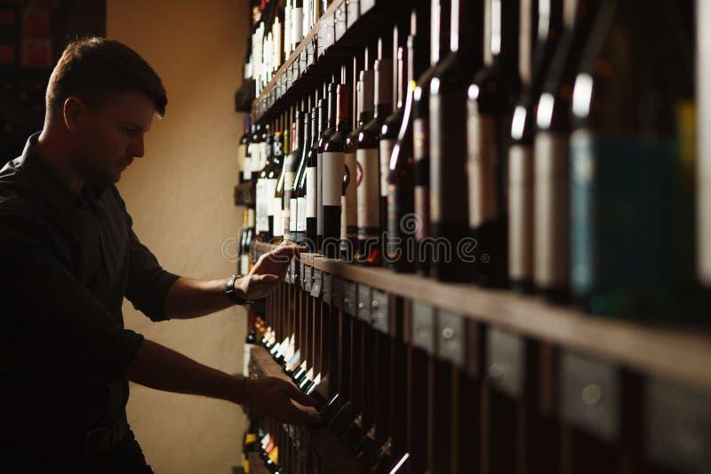 Sommelier que toma una de botellas del s?tano de madera imagen de archivo