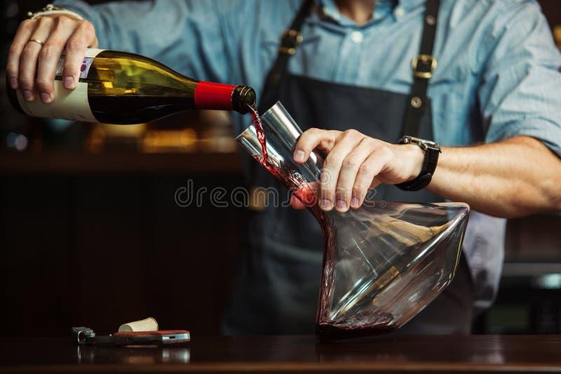 Sommelier que vierte el vino rojo en garrafa para hacer color perfecto imagenes de archivo