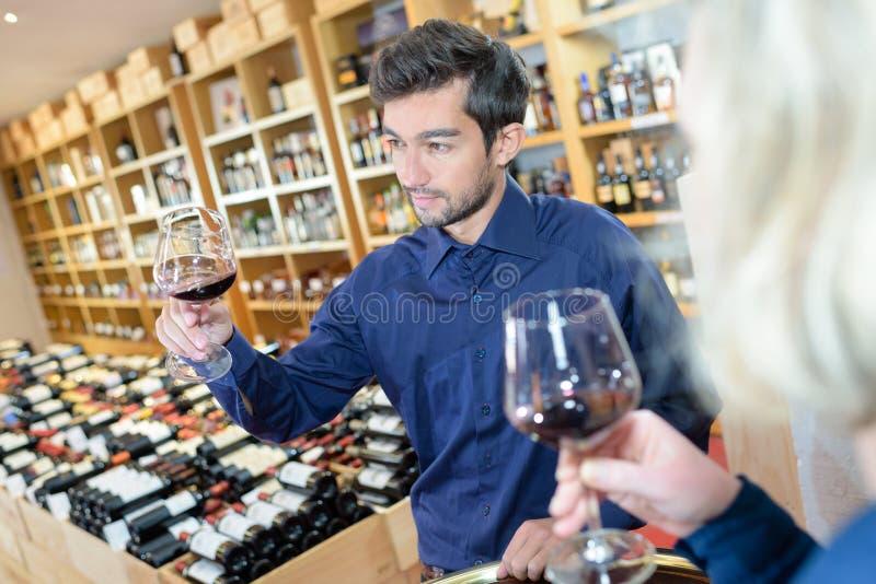 Sommelier- und Kundenprobierenweinglas lizenzfreies stockfoto