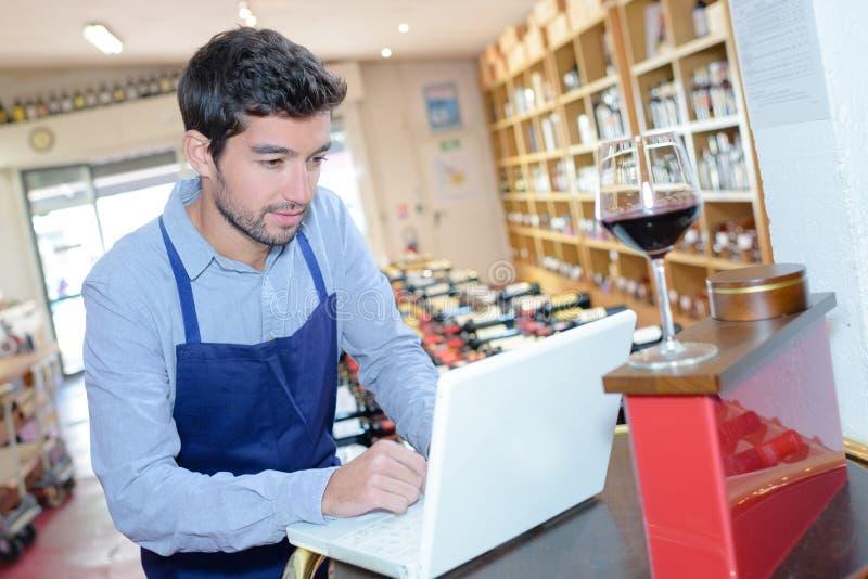 Sommelier w frontowym laptopie przy wino lochem zdjęcia stock